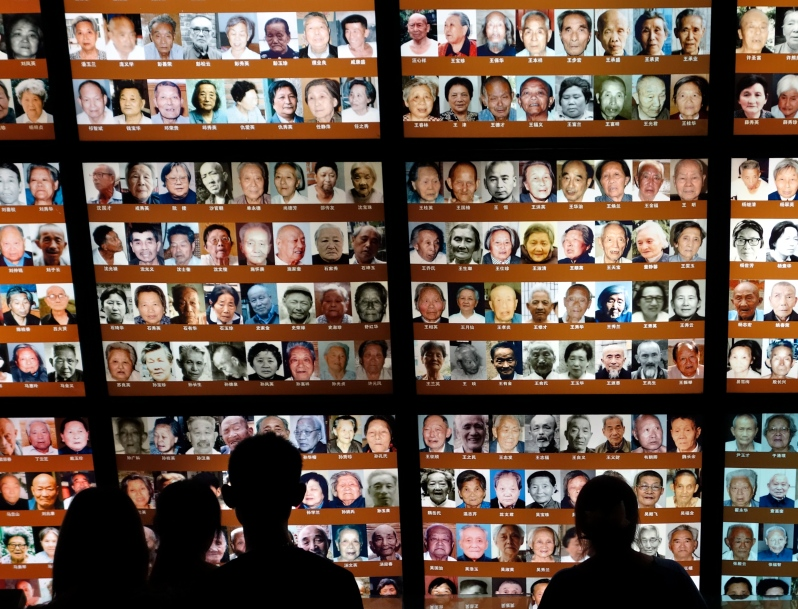 Young people view images of survivors of the Nanjing Massacre Memorial Hall in China on Dragon Boat Festival Holiday, 2013.