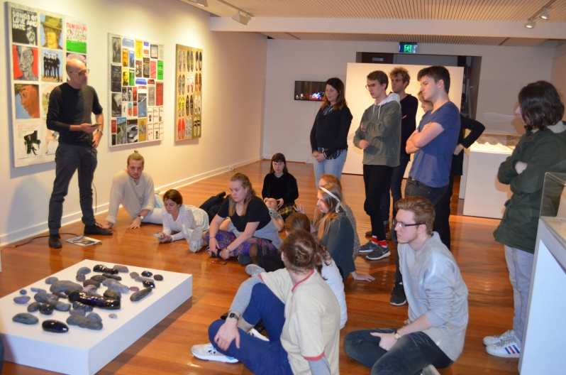 Dr Anthony Lyons and students at The George Payton Gallery listen to compositions in response to works in the exhibition.