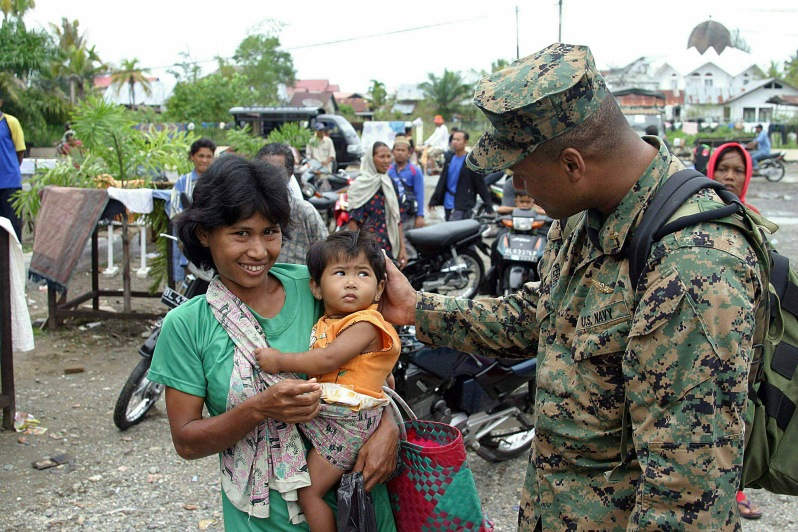 Figure 3. Head Surgeon of the Combined Support Group-Indonesia, US Navy Lieutenant Commander Loring Issaac Perry, takes a moment to comfort an Indonesian women and her child who lost everything they had during the Tsunami in the city of Meulaboh on the island of Sumatra, Indonesia. Photograph attributed to Pfc. Nicholas T. Howes, USMC / 1 January 2005.